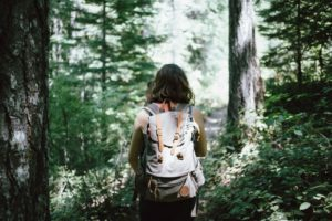 Woman with backpack walking through forest as she travels the world after graduation