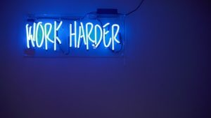 "Blue neon sign that reads ""Work Harder"" suggesting to get a job straight after graduation"