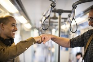 Two friends fist bump as they use their commute to be more socially productive